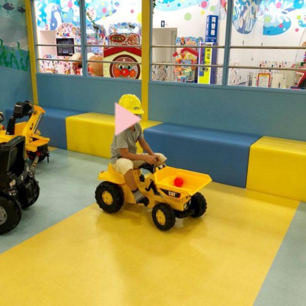 黄色の工事現場の車にヘルメットをかぶった男の子
