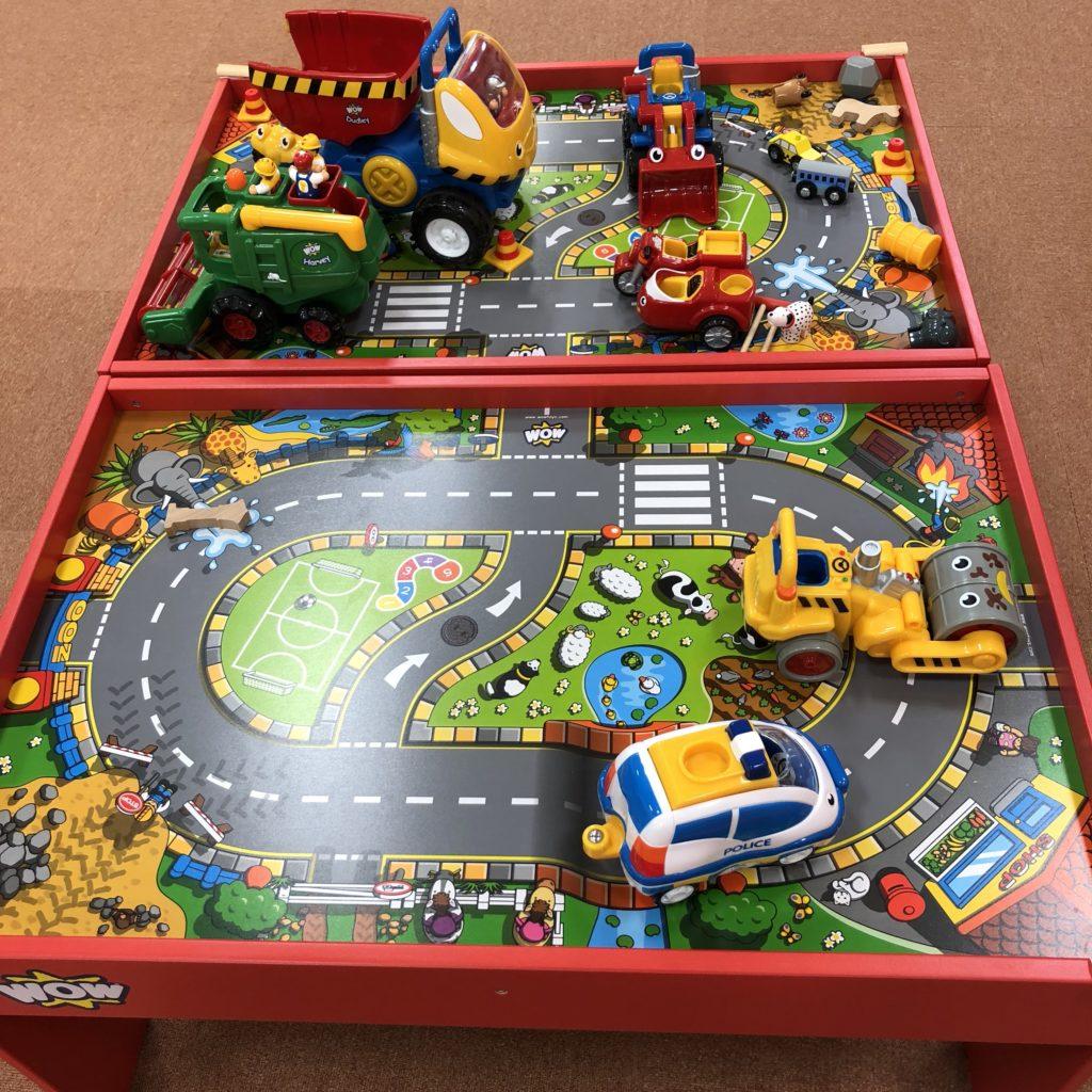 トイテーブルに並んだ電車や車のおもちゃ