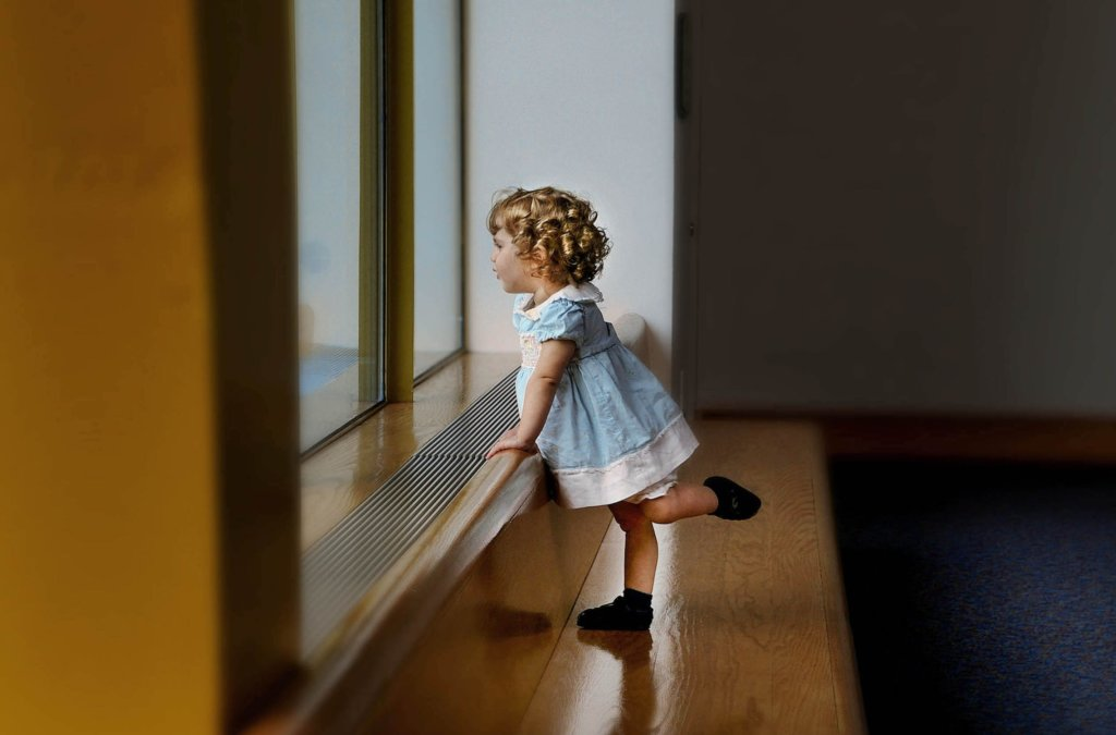 窓から外を眺める少女